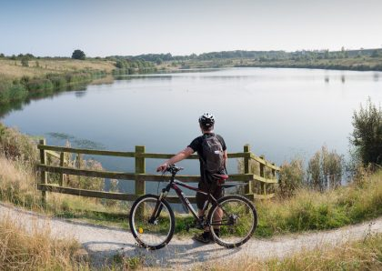 Man standing next to a bicycle overlooking a tranquil lake
